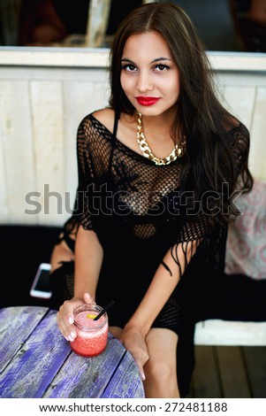 Portrait of gorgeous young woman sitting outdoors in beach cafe and drinking freshly-juiced juice, happy cheerful woman smiling friendly looking to you, charming female enjoying fruit smoothie - stock photo