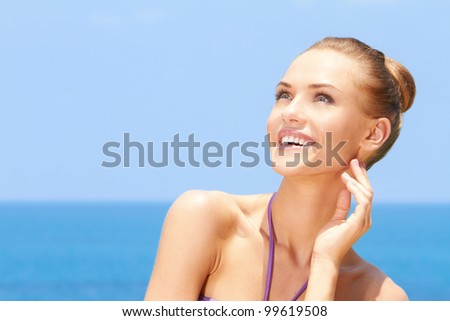 Portrait of gorgeous young woman smiling while looking at her right - stock photo
