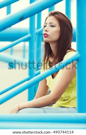Portrait of gorgeous young woman wearing yellow-green handmade knitted top and posing between blue metal constructions. Urban style. Close up. Outdoor shot
