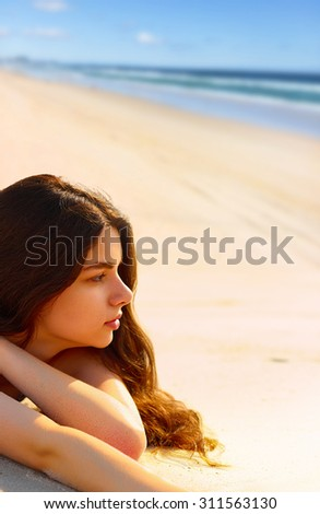 Portrait of gorgeous young woman  while relaxing on beach - stock photo