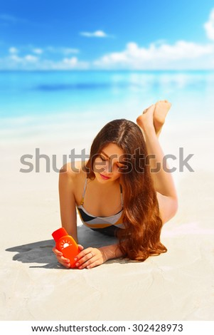 Portrait of gorgeous young woman  while relaxing on beach and holding sunscreen bottle