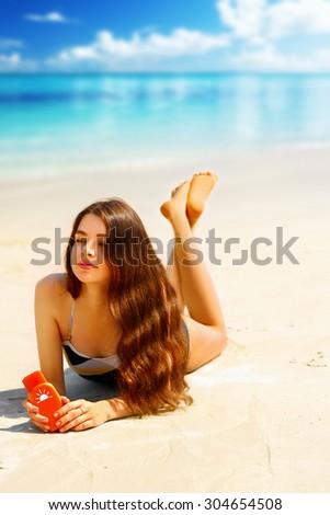 Portrait of gorgeous young woman  while relaxing on beach and holding sunscreen bottle - stock photo
