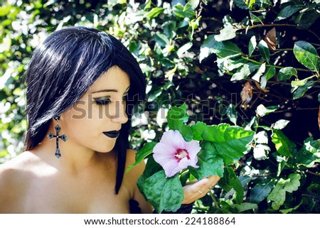Portrait of gothic style girl with flower - stock photo