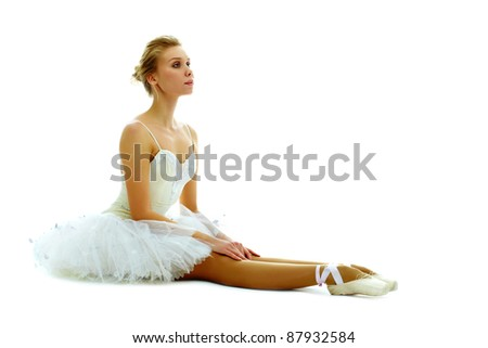 Portrait of graceful ballerina seated with stretched legs on white background