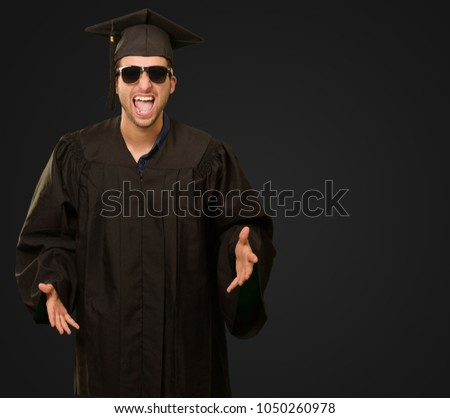 Portrait Of Graduate Man Shouting On Black Background