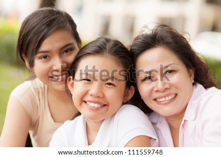 Portrait of granddaughters with grandmother smiling at camera outdoors - stock photo