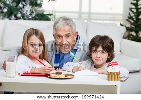 Portrait of grandfather and children with cardpapers at home