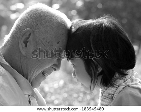 Portrait of grandfather and granddaughter, smiling at each other , BLACK AND WHITE , B&W - stock photo