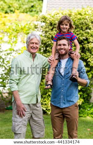 Portrait of grandfather standing with son carrying grandson at yard