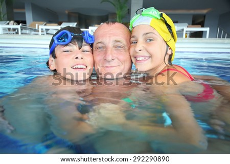 Portrait of grandfather with boy and girl in the outdoor swimming pool  - stock photo