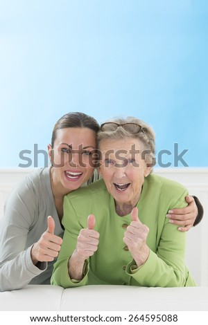 Portrait of grandmother and granddaughter showing thumbs up - stock photo