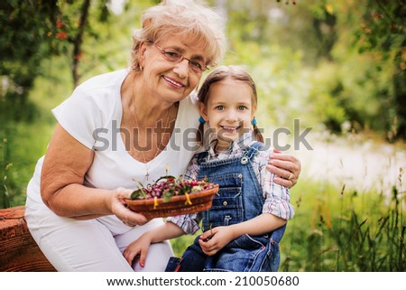 Portrait of grandmother with granddaughter holding cherries - stock photo