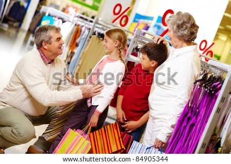 Portrait of grandparents and grandchildren in clothing department - stock photo