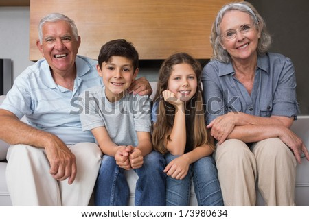 Portrait of grandparents and two kids sitting on sofa in the living room at home - stock photo