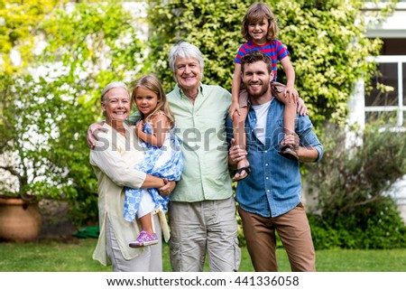 Portrait of grandparents with grandchildren and son at yard - stock photo