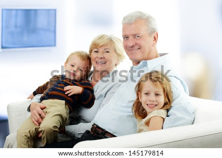 Portrait Of Grandparents With Grandchildren Relaxing Together On Sofa at Home - stock photo
