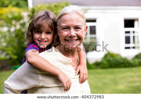 Portrait of granny piggybacking grandson in yard