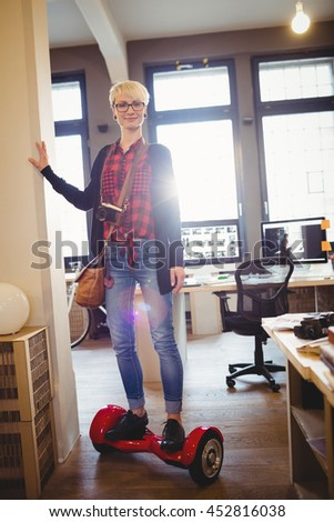 Portrait of graphic designer standing on hover board in office - stock photo