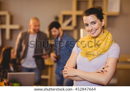Portrait of graphic designer with arms crossed while colleagues interacting in background - stock photo