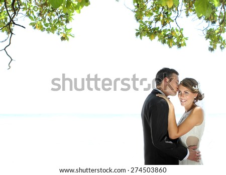 portrait of groom kissing his beautiful bride with copy space - stock photo
