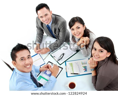 Portrait of group executives meeting around a table with many paperwork - stock photo
