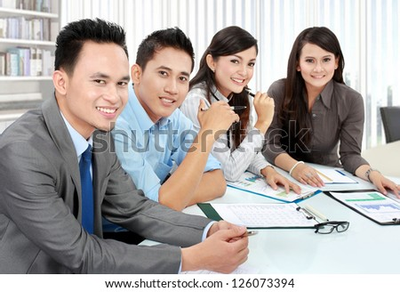 Portrait of group executives meeting around a table with many paperwork