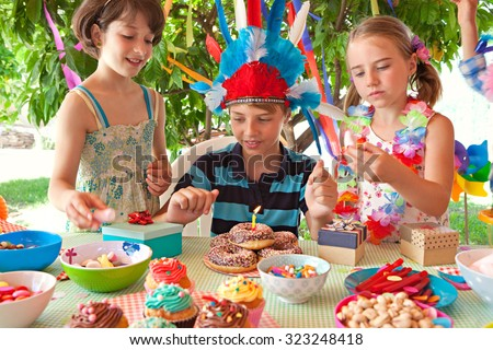 Portrait of group of children dressing up in fancy dresses at a colorful birthday party in a home garden. Bright decorations, candle cake, joyful expressions outdoors lifestyle. Kids activities fun. - stock photo