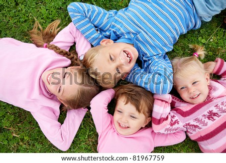 portrait of  group of children happily laughing and lying on the grass