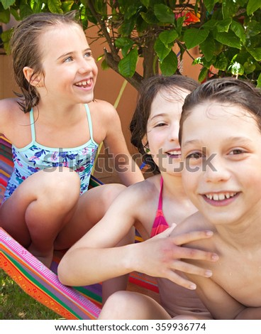 Portrait of group of children sharing a hammock together, smiling at camera wearing swimming costumes with wet hair on a summer holiday in a home garden, outdoors. Kids fun lifestyle, house exterior.