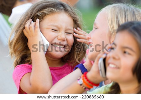 Portrait of group of childrens using mobile phones in the park. - stock photo