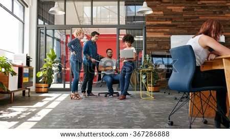 Portrait of group of creative people having a meeting with a laptop in a modern office. Business people having relaxed conversation over new project. - stock photo