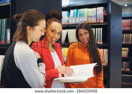 Portrait of group of female students standing in library sharing their study notes. College students preparing for final exams. - stock photo