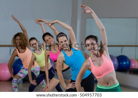 Portrait of group of fitness team performing stretching exercise in fitness studio