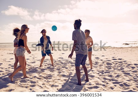 Portrait of group of happy friends having fun on the beach and playing with ball on a summer day. - stock photo