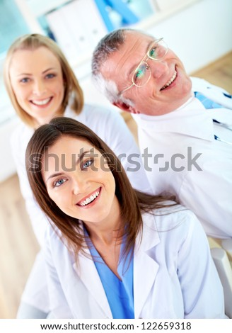 Portrait of group of happy practitioners looking at camera - stock photo