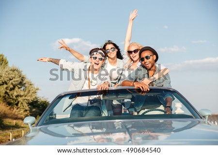 Portrait of group of happy young people in cabriolet