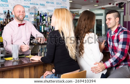 Portrait of group of people at the bar. A couple and alone attractive woman are sitting at the bar while the smiling bartender is pouring cocktail in a glass - stock photo