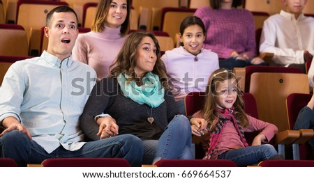 Portrait of group of people watching exciting movie in cinema house