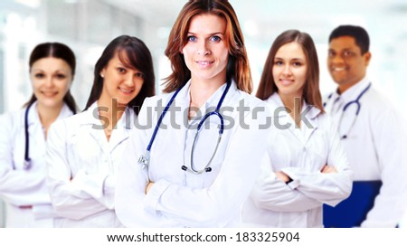 Portrait of group of smiling hospital colleagues standing together - stock photo