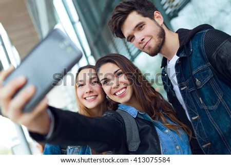 Portrait of group of students having fun with smartphones after class.
