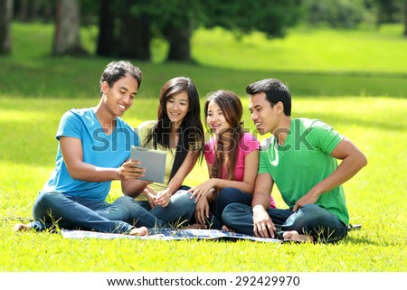 Portrait of Group of students studying in the park using tablet PC - stock photo