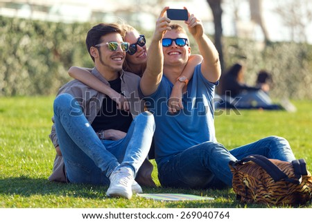 Portrait of group of students taking photos with a smartphone in the street. - stock photo
