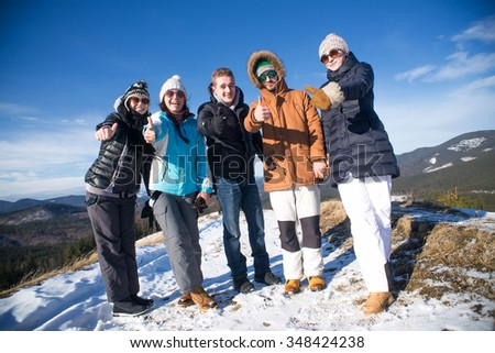 Portrait of Group of teenagers showing thumbs up and having a good time in winter.