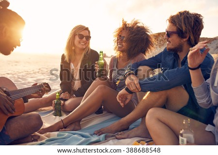 Portrait of group of young friends having a party on the beach in evening. Men and women drinking beers and listening to friend playing guitar. - stock photo