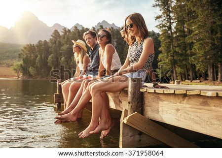 Portrait of group of young people sitting on the edge of a pier, outdoors in nature. Friends enjoying a day at the lake. - stock photo