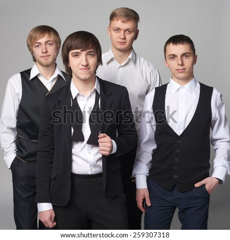 Portrait of group young men standing over gray background looking at camera - stock photo