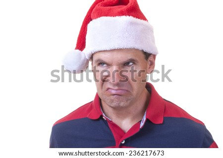 Portrait of grumpy Caucasian man wearing casual shirt and red Santa hat making ugly grinch face on white background