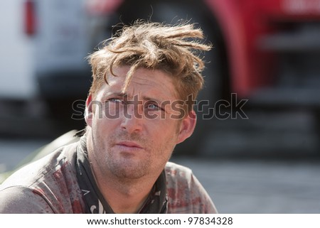 Portrait of grungy unshaven man outdoors during the daytime. - stock photo