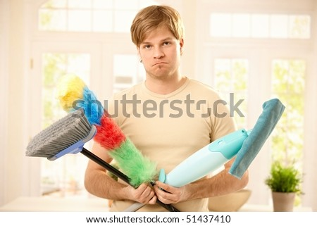 Portrait of guy upset with housework, holding broom, mop and flannel in bright living room. - stock photo