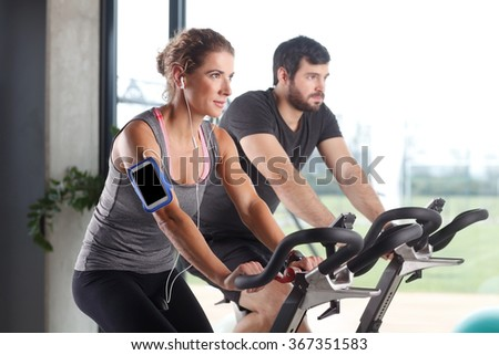 Portrait of gym members participating in a spinning class while training together at fitness center. Sporty woman listening music at her mobile phone.
